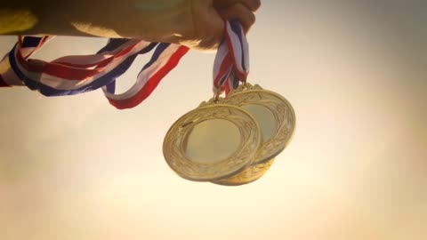 hand holding gold medal up - medal stock videos & royalty-free footage