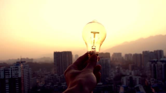 vídeos de stock e filmes b-roll de hand holding lamp at sunset - lâmpada elétrica