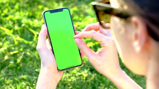 hand holding mobile phone at the park with green screen - liquid crystal display stock videos & royalty-free footage