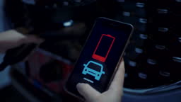 Hand holding mobile phone displaying electric charging progress bar