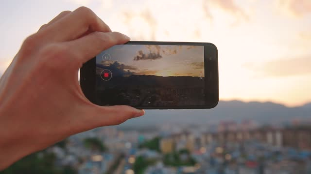 hand holding mobile phone recording city sunset - photographing stock videos & royalty-free footage