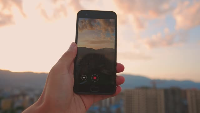 hand holding mobile phone recording city sunset - filming stock videos & royalty-free footage