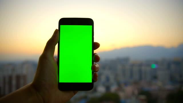 vídeos de stock, filmes e b-roll de mão que prende o telefone móvel com tela chave dos chroma - photographing