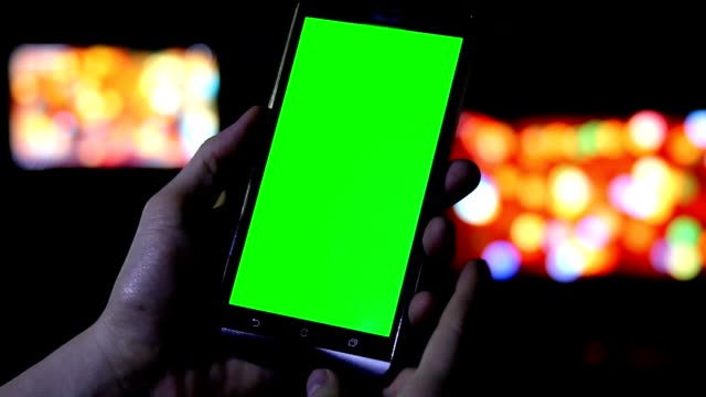 hand holding mobile phone with green screen at night in the dark