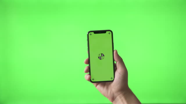 hand holding modern smartphone on green screen bg - telephone stock videos & royalty-free footage