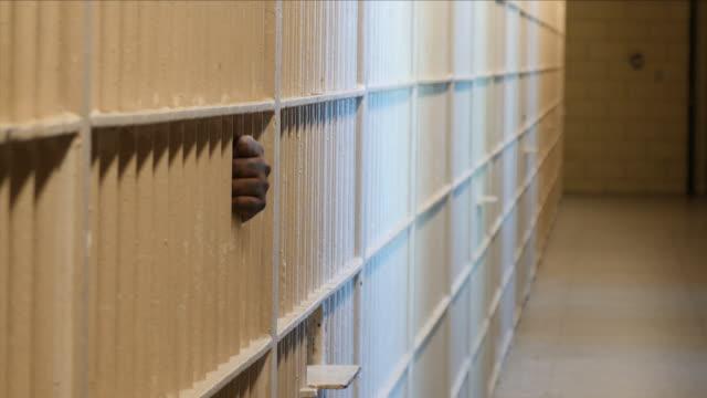 vídeos de stock, filmes e b-roll de hand holding prison bars - grade de prisão