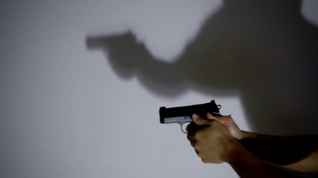 vídeos de stock e filmes b-roll de 4k ms hand holding semi-autometic handgun at night with shadow on white wall. - guardar