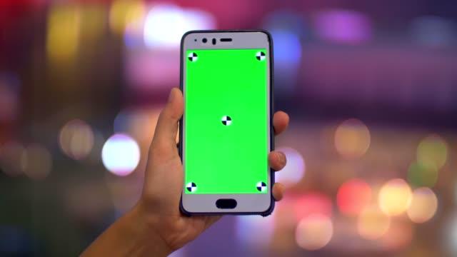 vídeos y material grabado en eventos de stock de cu: mano smartphone en el fondo de la noche ciudad luz bokeh - mensaje de móvil