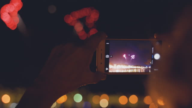 hand holding smartphone filming firework - hand back lit stock videos & royalty-free footage
