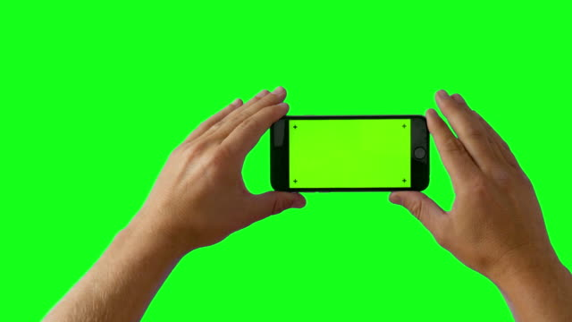 hand holding smartphone on green screen bg - 4k - photo shooting stock videos and b-roll footage