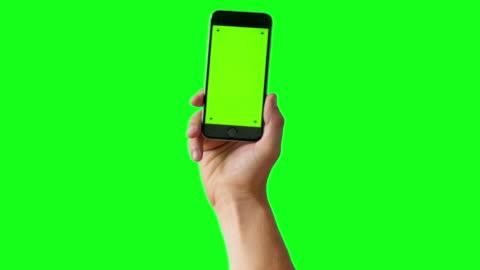 hand holding smartphone on green screen bg - 4k - human hand stock videos & royalty-free footage