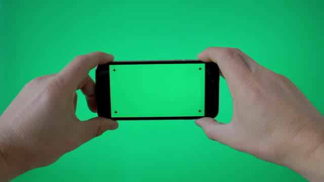 vídeos de stock e filmes b-roll de hand holding smartphone (landscape) on green screen bg - horizontal