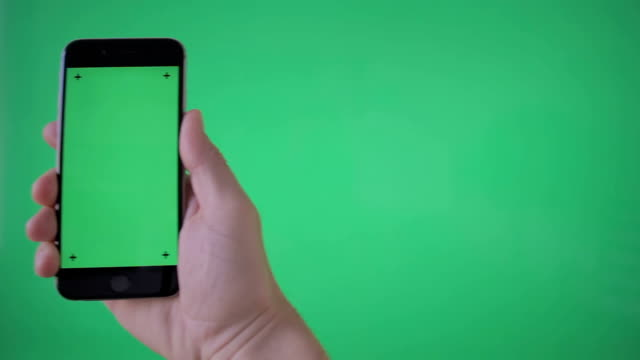 hand holding smartphone (portrait) on green screen bg - human hand stock videos & royalty-free footage