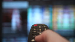 Hand holding the TV remote control smart television