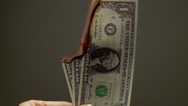 cu zo hand holding three u.s. one dollar bills as they burn  - unknown gender stock videos & royalty-free footage