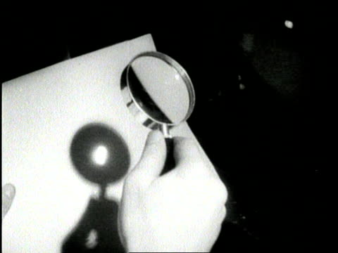 a hand holds a magnifying glass and the sun burns a hole in a paper - magnifying glass stock videos & royalty-free footage