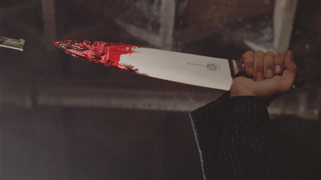 hand holds bloody knife, stabs downward - evil stock videos & royalty-free footage