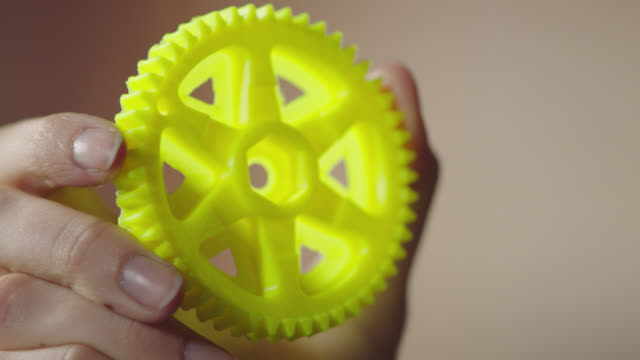 ECU. Hand holds bright yellow gear created with 3D printing technology.