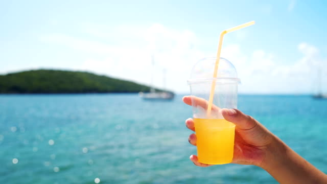 hand holds cup of fresh orange juice - juice drink stock videos & royalty-free footage