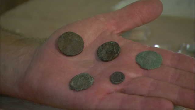 A hand holds several antique coins.