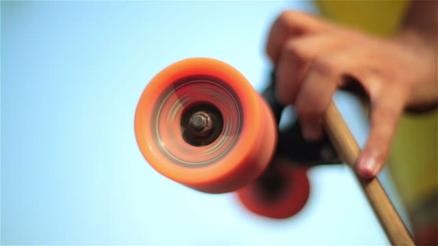 hand holds skateboard with wheels still spinning - wheel stock videos and b-roll footage