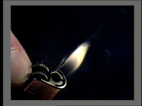 a hand ignites a cigarette lighter. - feuerzeug stock-videos und b-roll-filmmaterial