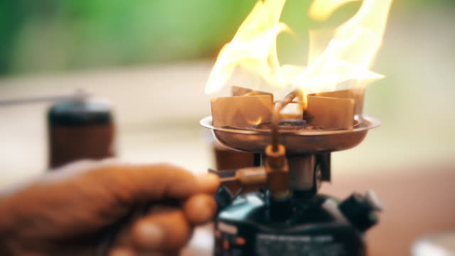 hand ignites on a mini burner stove outdoors. - camping stove stock videos and b-roll footage