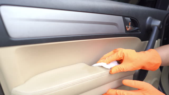 hand in glove wiping down door handle surfaces of car interior cleaning covid-19 virus in the garage at home. - car interior stock videos & royalty-free footage