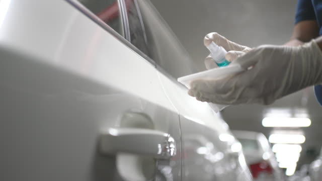 vídeos de stock e filmes b-roll de hand in glove wiping down door handle surfaces of white car  cleaning covid-19 virus in parking lot of apartment - limpo