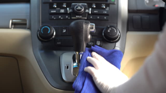 hand in glove wiping down on surfaces of the shift knob of automatic gearshift  for cleaning covid-19 virus - gearshift stock videos & royalty-free footage