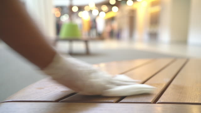hand in glove wiping down public bench surfaces for cleaning covid-19 virus in shopping mall or station - cleaning glove stock videos & royalty-free footage