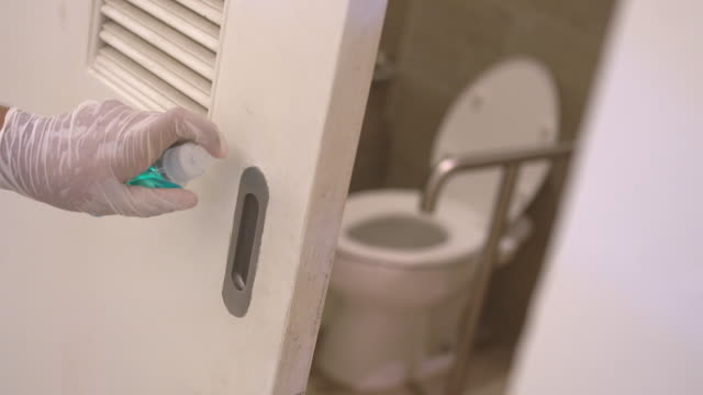 hand in glove wiping down public restroom toilet slide door surfaces for cleaning covid-19 corona virus - rubbing alcohol stock videos & royalty-free footage