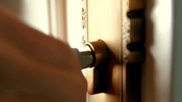 hand inserting key into keyhole and opening door - sistemi di sicurezza video stock e b–roll