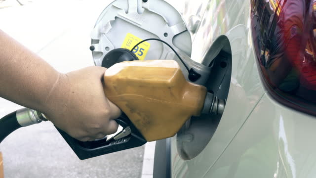 hand inserting petrol pump nozzle into tank of car and beginning to pump fuel - petrol tank stock videos and b-roll footage