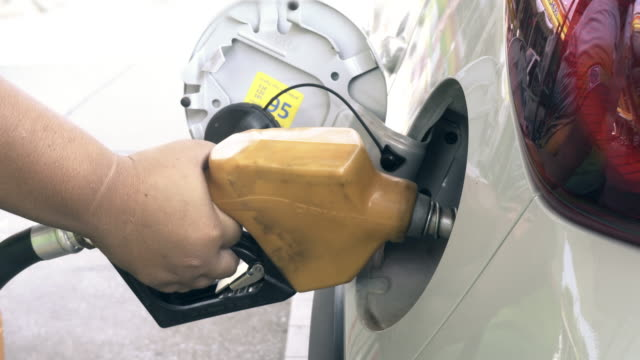 hand inserting petrol pump nozzle into tank of car - petrol tank stock videos and b-roll footage