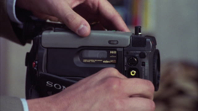 vídeos de stock, filmes e b-roll de a hand inserts a cassette and a jack into a sony video camera. - filmando