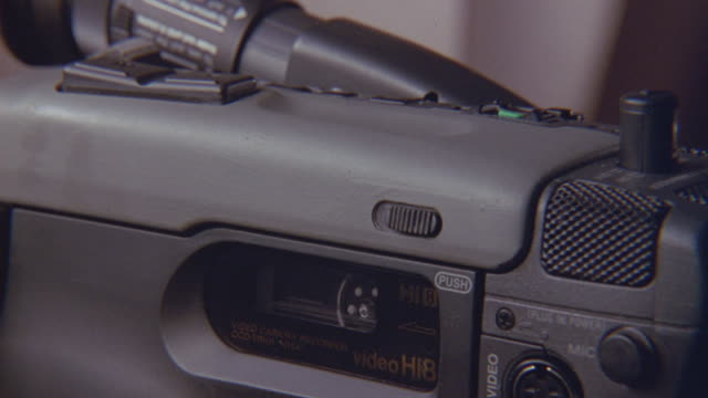vídeos de stock e filmes b-roll de a hand inserts a videotape into a video camera then starts to record. - videocassete