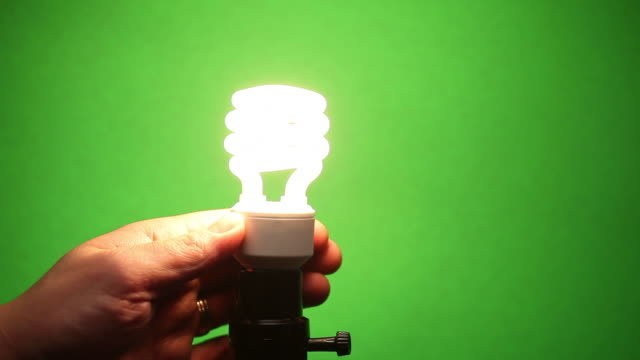 vídeos de stock, filmes e b-roll de mão for instalado e remove cfl e luz de led bulb - energy efficient