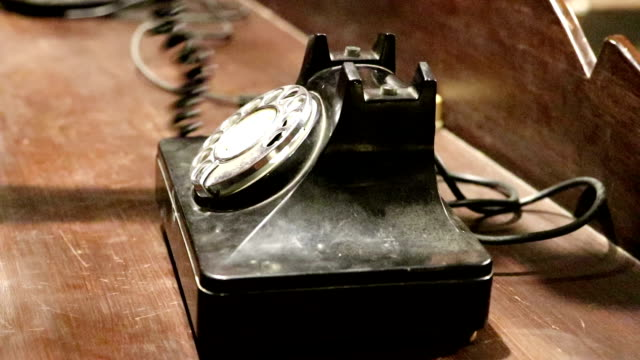 A hand is dialing the old phone.
