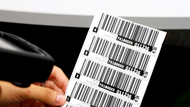 Hand is holding a handheld and read the barcode.