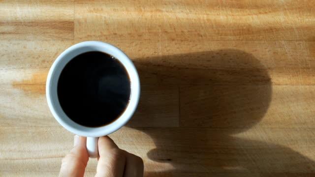 vídeos de stock, filmes e b-roll de a mão está derramando o café preto a um copo com vapor natural nele que toma então o copo - xícara de café