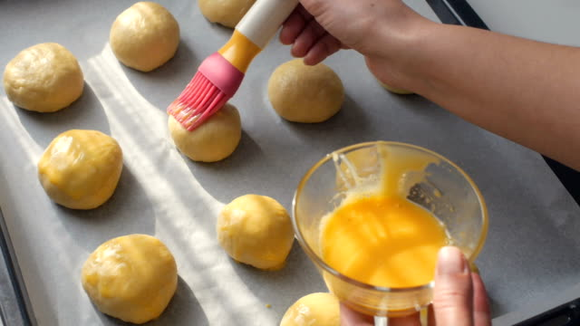 dolly: hand is putting some egg yolk on dough buns with a brush as preparation before baking them in the oven - baking tray stock videos & royalty-free footage
