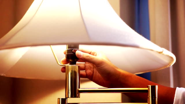 hand is switching on and off the table lamp in a living room. - electric lamp video stock e b–roll