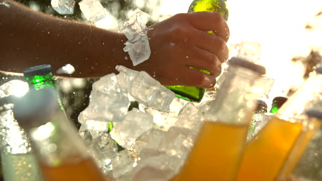 super slo mo hand is taking a bottle of beer from a cooler - cooler container stock videos & royalty-free footage