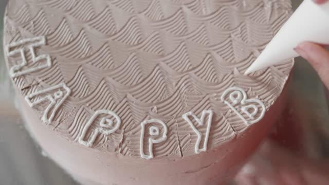 vidéos et rushes de la main écrit des mots heureux d'anniversaire sur le gâteau - anniversaire