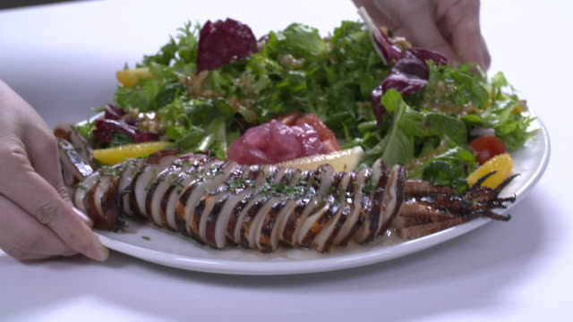 stockvideo's en b-roll-footage met hand laying squid salad on the table - gedekte tafel