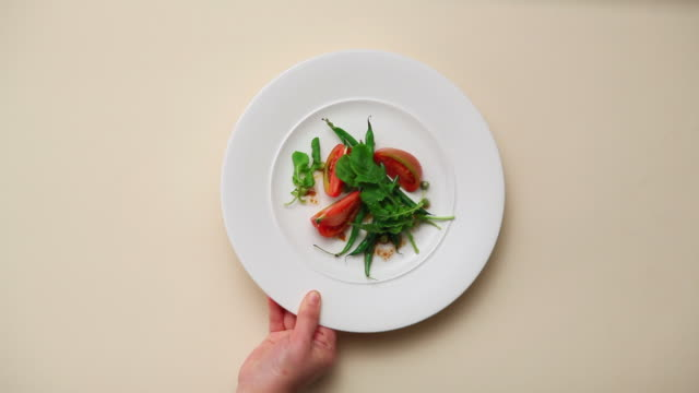 CU Hand laying tomato salad on white backdrop / Seoul, South Korea