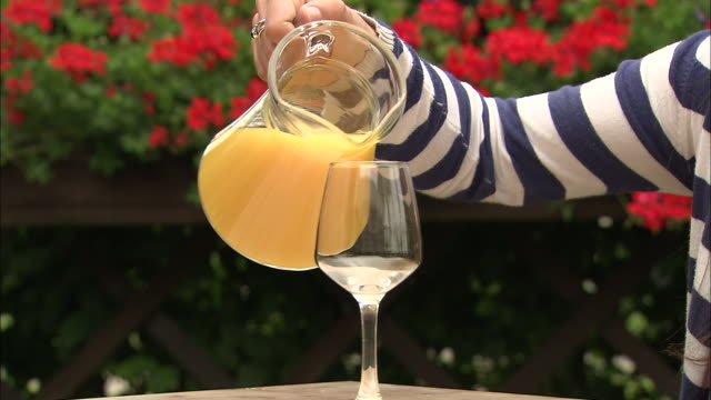 a hand lifts a pitcher of orange juice, pours it into a glass, and replaces it on a table. - refreshment stock videos & royalty-free footage