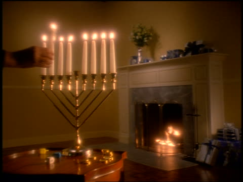 vídeos de stock, filmes e b-roll de hand lighting candles on menorah on table in living room with fireplace in background - candelabro