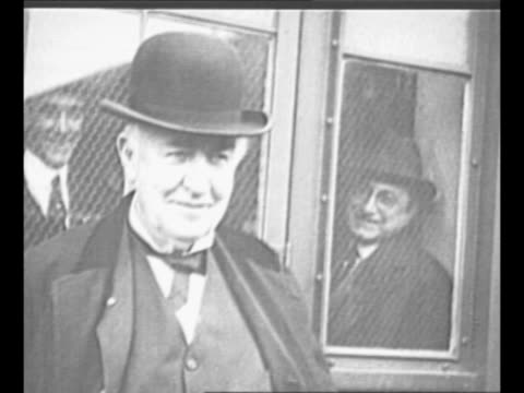 CU hand lowers lever light bulb illuminates / montage inventor Thomas Edison stands outside building as men inside watch through window he smiles...